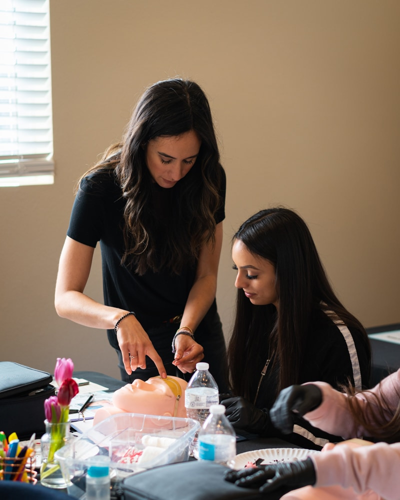 Bay Area Microblading Training, teacher giving a student some advice on test piece